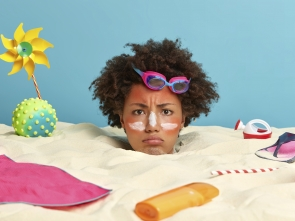 young-woman-head-with-sunscreen-cream-on-face-surrounded-by--accessories